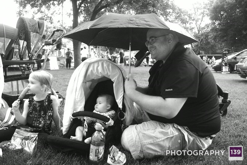 Shawn protecting his progeny during a brief bit of precipitation during Ogden Fun Days. Further proof that he is bona fide.